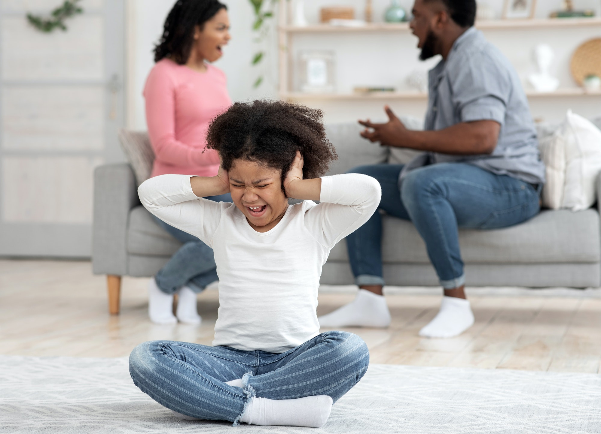Childhood Traumas. Little Black Girl Covering Ears Not To Hear Parents Quarrels