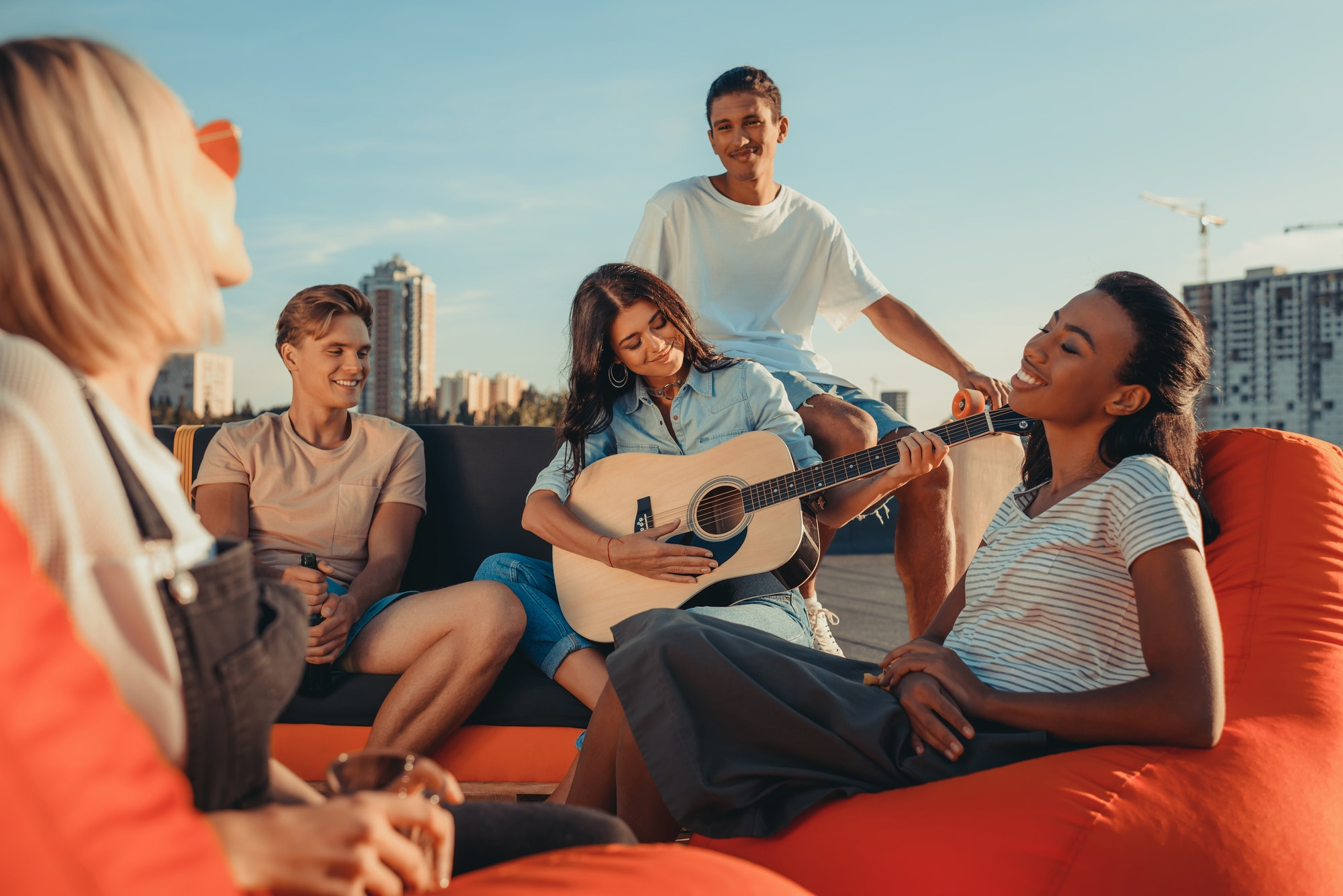 young girl playing guitar for group of happy friends